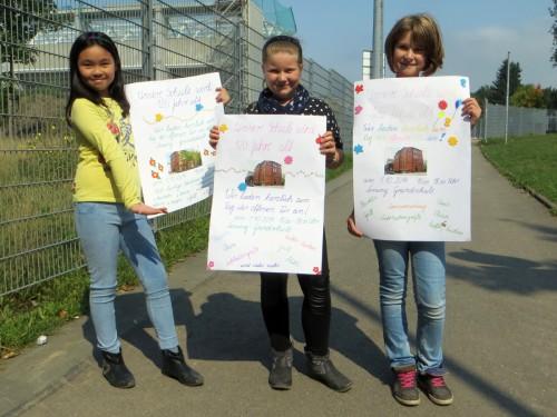 Die drei Schülerinnen warben Eckart Roßberg mit selbst gemalten Plakaten für das Jubiläumsschulfest.